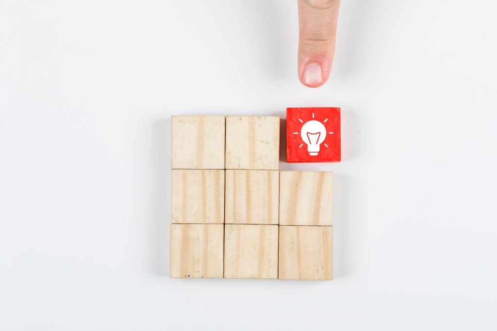 Conceptual of idea hand pointing the idea. with wooden blocks on white background top view. horizontal image