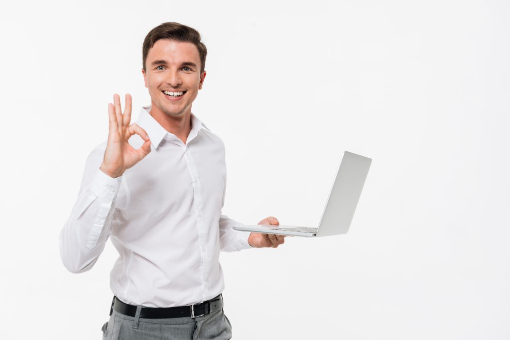 Portrait of a smiling handsome man holding laptop computer while showing ok gesture and looking at camera isolated over white background